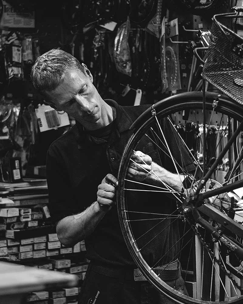 Cykelmekaniker i cykelværksted lapper en cykel